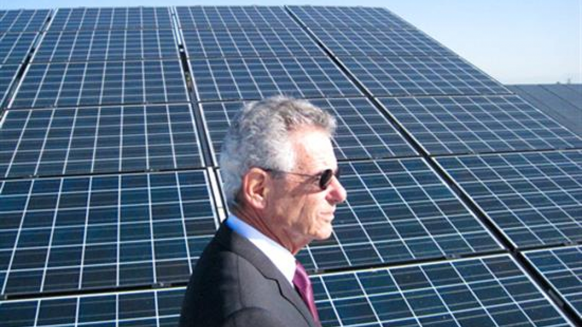 Congressman Lowenthal standing in front of a solar panel