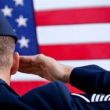 a military veteran saluting the U.S. flag